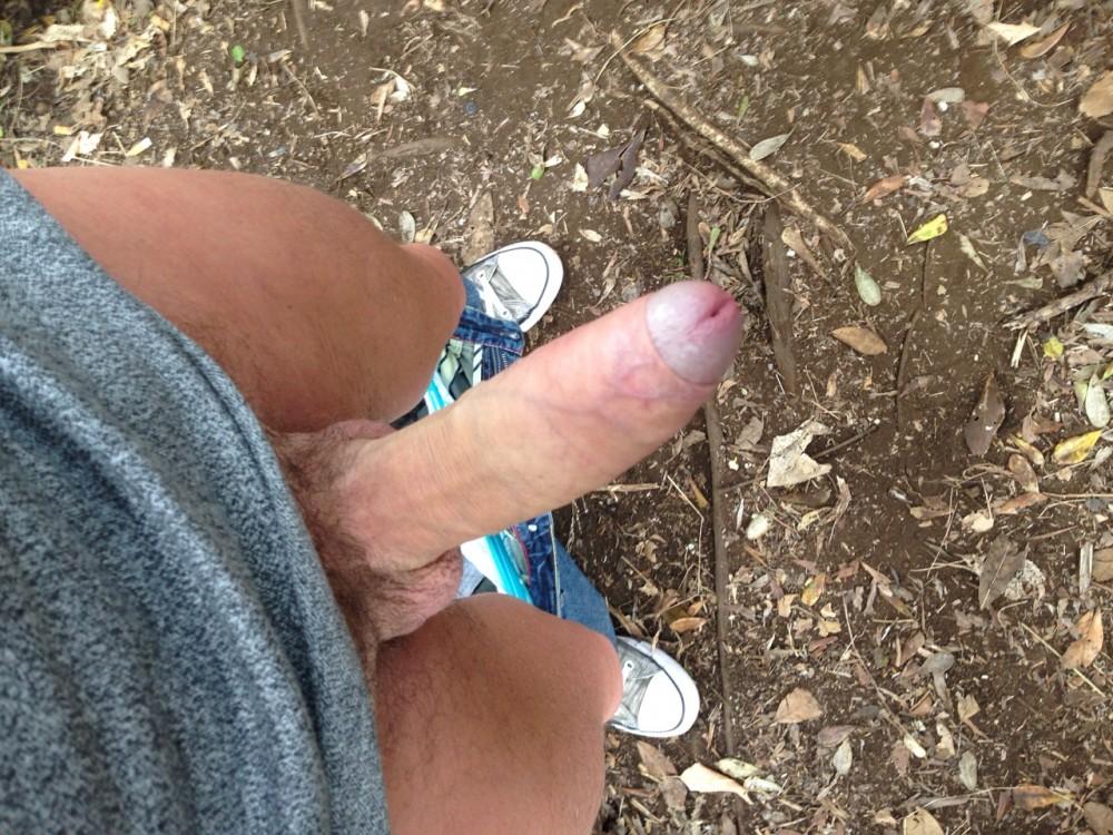 Man staat buiten met stijve lul en half ontblote eikel